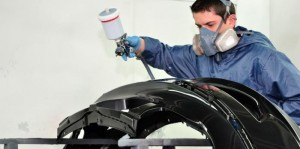 man painting auto part